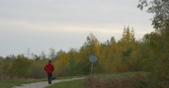 Man in Red Jacket Walking his Dog on Footpath in Park or Forest Road Stock Footage
