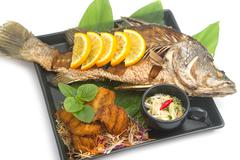 Fired fish with fishsauce and mango salad , Thai food  favorite Stock Photos