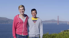 Portrait Of Gay Couple, Golden Gate Bridge In Background, They Kiss On Cheek Stock Footage
