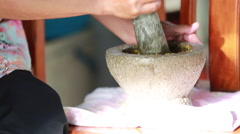 Unidentified human hand pounding spices in stone mortar, traditional Thai curry Stock Footage
