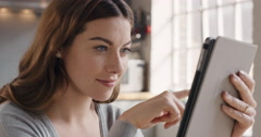 Happy beautiful woman using digital tablet browsing the internet staying Stock Footage