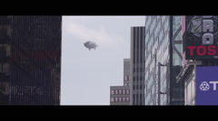 Blimp flying between buildings (farther) Stock Footage