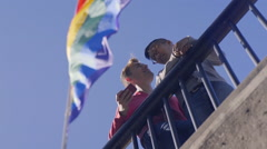 Happy Gay Couple Stand Under Gay Pride Flag And Take Selfies Together Stock Footage