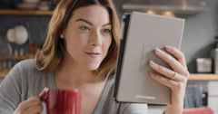 Beautiful woman talking to friends on internet using digital tablet app at home - stock footage