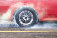 Race car burns rubber off its tires for the race Stock Photos