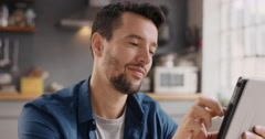 Happy man using digital tablet browsing the internet staying connected at home Stock Footage