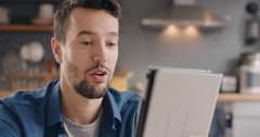 Happy man talking to his friend online using digital tablet app at home Stock Footage