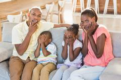 Portrait of a family of four watching tv Stock Photos