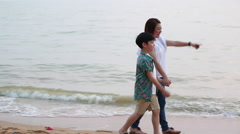 Asian family mother and son walking and looking sunset with sea background Stock Footage