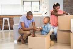 Stock Photo of Family unwrapping things in new home