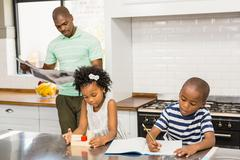 Children playing and drawing in the kitchen Stock Photos