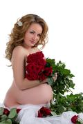 Nude pregnant woman posing with rose bouquet Stock Photos