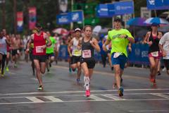 Exhausted Runners Cross Finish Line At Atlanta Peachtree Road Race - stock photo