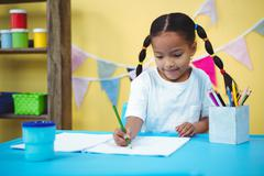 Smiling girl drawing in her colouring book - stock photo