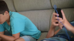 Boy relaxing with phone in living room - stock footage