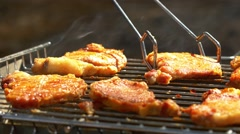 Grilled pork steaks over flames and coals, on the brazier, turn slices, close up Stock Footage