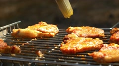 Grilled pork steaks over flames and coals, on the brazier, slush, close up, side Stock Footage