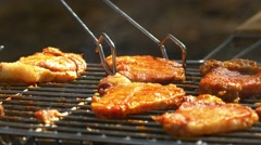 Grilled pork steaks over flames and coals, on the brazier, slush and turn, close Stock Footage