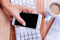 Businesswoman using her smartphone on desk Stock Photos