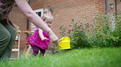 4K Cute little toddler girl watering the plants in the garden Stock Footage