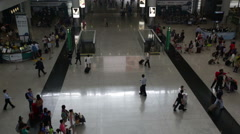 Overhead airport hall people rushing 1 man in center, Hong kong Stock Footage