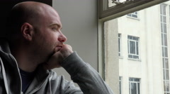 Depressed thoughtful young man deep in his problems and looking out the window  Stock Footage