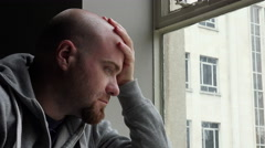 Sad desperate and depressed young man near the window Stock Footage