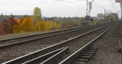 Man in Warm Ushanka Hat Jacket And Earphones is Walking by Railroad Railway by Stock Footage