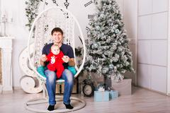 Stock Photo of Dad and son at home with christmas tree
