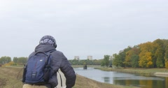 Man in Warm Ushanka Hat in Warm Jacket Backpacker is Riding BicycleAway by Road Stock Footage