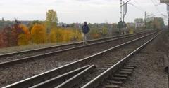 Man in Warm Ushanka Hat Jacket And Earphones is Walking by Railroad Railway Stock Footage