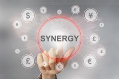 business hand pushing synergy button - stock photo