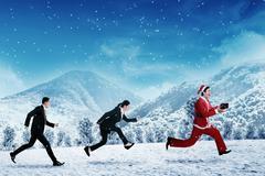 Business people chasing santa claus Stock Photos