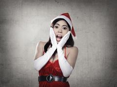 Shocking woman in santa claus costume - stock photo