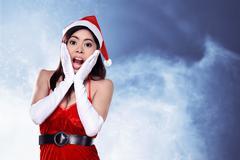 Shocking woman in santa claus costume - stock photo