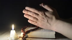 Praying hands over a holy book Stock Footage
