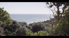 Looking through coastal bush with a view of Wategos Beach, Byron Bay Stock Footage