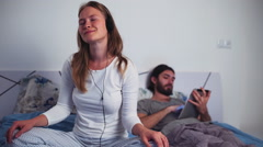 Female listening to music in headphones and male using a tablet in bed Stock Footage