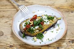 Roast aubergine with goats cheese, kale and sun dried tomatoes Stock Photos