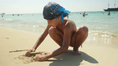 Child playing with sand on the beach. - stock footage