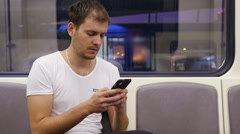 Man use type a phone internet in train with city evening lights behind a window Stock Footage