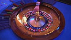 Roulette wheel - groupier spins the wheel - ball lands on field 14 red Stock Footage
