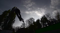 Stock Video Footage of Silhouette of jumper, performing BMX mountain bike sport jump. Slow Motion 400