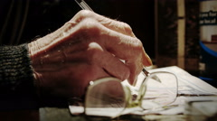 Old man's hand holding a pen and making sudoku or crosswords  Stock Footage
