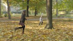 Sisters running in the park through the yellow fallen leaves,autumn seasons. Stock Footage
