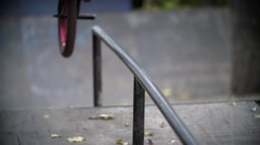 Biker doing peg grind down the hand rail over the stairs Slow Motion 400 fps Stock Footage