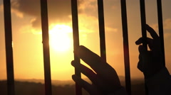 hands behind bars seeking freedom at sunset - stock footage