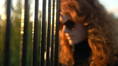 sad woman leaning an iron fence looking the sunset - stock footage