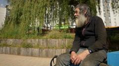Old man, poor man, sad elderly man sitting alone in a city park  Stock Footage