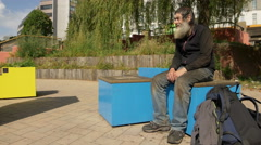 Old homeless man sitting in a city square waiting for charity  Stock Footage